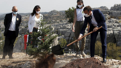 French President Emmanuel Macron plants a cedar with members of the NGO Jouzour Loubnan in Jaj, near Beirut, Tuesday Sept. 1,…