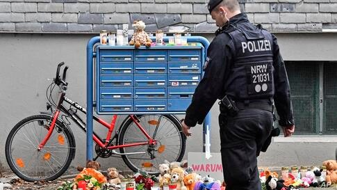 Police passes candles and teddy bears at the entrance of a house where five dead children were found in Solingen, Germany,…