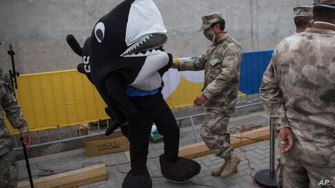 A marine helps a comrade dressed as their mascot, a shark, before the start of house-to-house coronavirus testing and food…