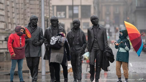 Members of the public wearing face masks stand near a statue of The Beatles in Liverpool, England, Monday Oct. 12, 2020, as…