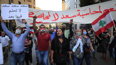 Anti-government protesters shout slogans during a protest to denouncing the naming of former Prime Minister Saad Hariri as a…