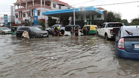 Local villagers travel through a flooded street following recent rains in Phnom Penh, Cambodia, Monday, Oct. 12, 2020. Flooding…