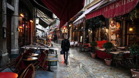 A woman walks by empty restaurants in the center of Lyon, central France, Friday, Oct. 2, 2020. French Health Minister Olivier…