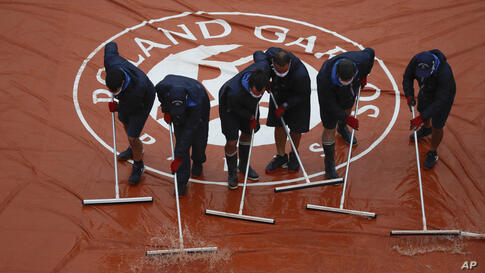 Stadium workers remove rain water from the cover of Suzanne Lenglen court as rain delayed fourth round matches of the French…