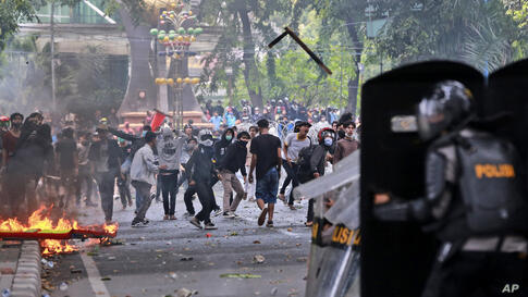 Protesters hurl debris at police during a rally against a controversial bill on job creation in Medan, North Sumatra, Indonesia…