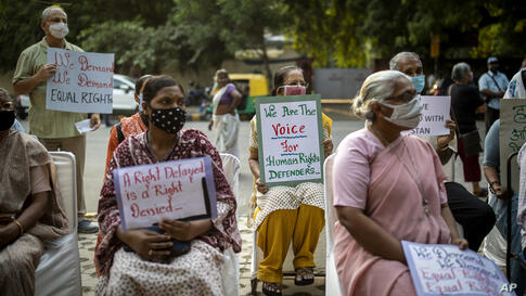 Indian civil society members hold placards during a protest demonstration against the alleged harassment of critics,…