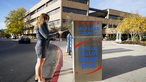 A woman inserts her ballot into an official ballot drop box Tuesday, Oct. 20, 2020, in Salt Lake City. (AP Photo/Rick Bowmer)