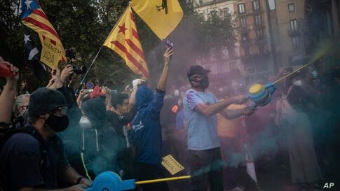 Demonstrators throw colored powder towards a police road block during a protest in Barcelona, Spain, Friday, Oct. 9, 2020…