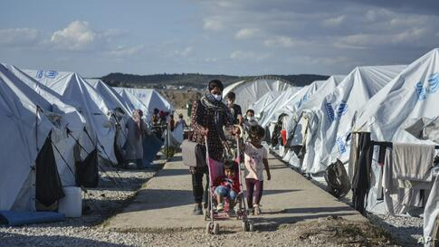 Migrants walk after a rainstorm at the Kara Tepe refugee camp, on the northeastern Aegean island of Lesbos, Greece, Wednesday,…