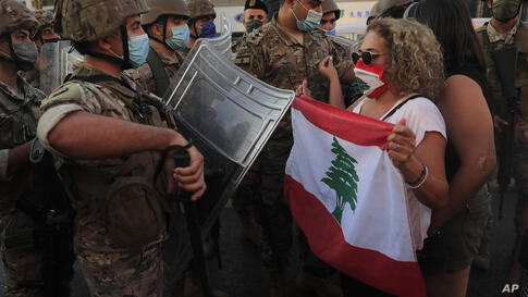 Lebanese army soldiers try to push back anti-government protesters blocking a main highway that links Beirut with north Lebanon…