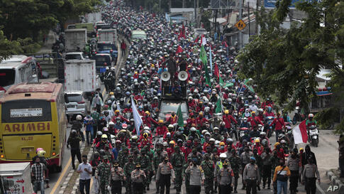 Indonesian workers march during a protest against a controversial omnibus bill on job creation, in Tangerang, Indonesia,…