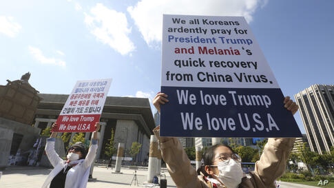 South Koreans Shon Ock-sun and Kim Min-kyung, right, hold up signs wishing for U.S. President Donald Trump and first lady…