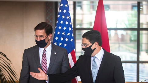 US Secretary of Defense Mark Esper, left, is received by Moroccan Foreign Minister Nasser Bourita, right, in Rabat, Morocco,…