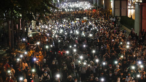 Pro-democracy demonstrators shine their mobile phone lights as they march to the German Embassy in central Bangkok, Thailand,…