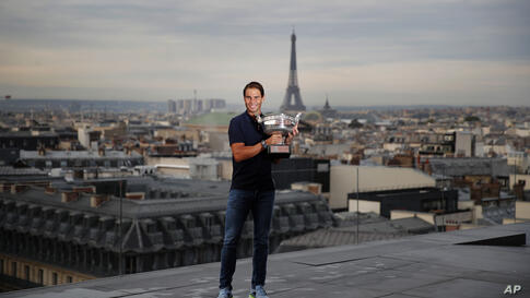 Spain's Rafael Nadal poses with his trophy during a photo call on the rooftop of Galeries Lafayette, Monday, Oct. 12, 2020,…