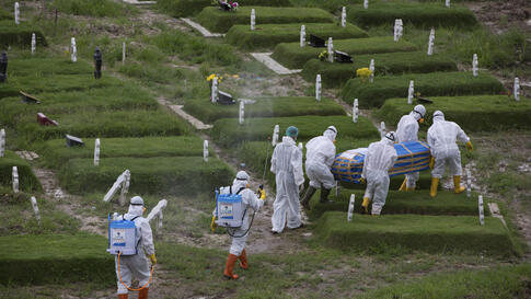 Workers in protective suits carry a coffin containing the body of someone who presumably died of the coronavirus for burial in…