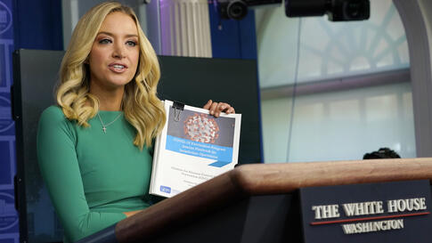 White House press secretary Kayleigh McEnany holds a coronavirus playbook speaks during a briefing at the White House in…