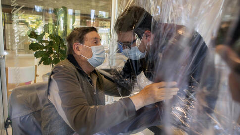 Relatives hug each other through a plastic film screen and a glass to avoid contracting COVID-19, at a nursing home in…