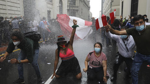 Supporters of former President Martin Vizcarra are kept back by a police water cannon as they protest near Congress where…