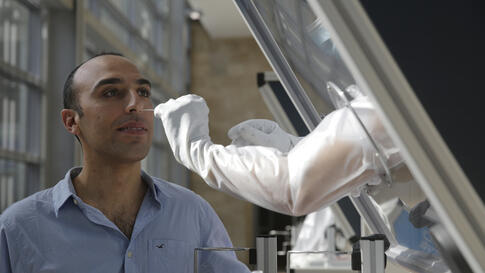 A technician demonstrates on an airport staffer how samples are taken, at a new on-site COVID-19 testing facility at Tel Aviv…