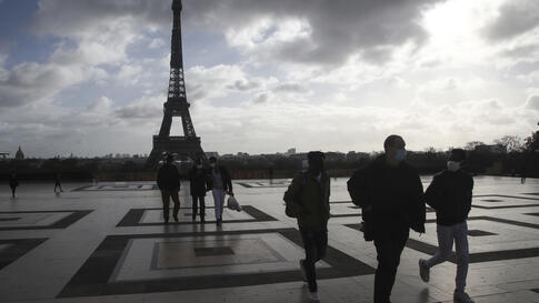 People wearing face mask, make their way on the Trocadero square, near the Eiffel Tower, in Paris, Thursday, Nov. 19, 2020…