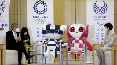 International Olympic Committee President Thomas Bach, left, talks with Tokyo Governor Yuriko Koike, right, during their…
