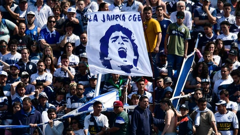 Fans hold up a banner of Diego Maradona, head coach of Gimnasia y Esgrima La Plata soccer team, prior to a local tournament…