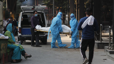 Health workers in personal protective equipment carry the body of a COVID-19 victim for cremation in New Delhi, India, Thursday…