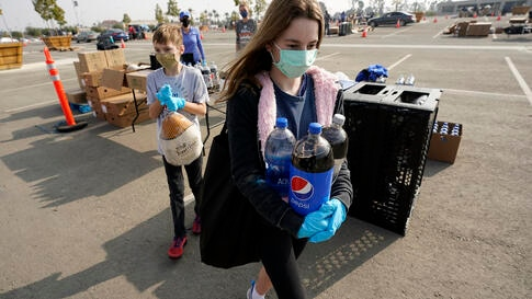 Claire Demoff, 13, foreground, and her brother Owen, 11, volunteer at a food distribution center set up at SoFi Stadium amid…