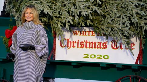 First lady Melania Trump stands next to the 2020 official White House Christmas tree after it arrived at the White House in…