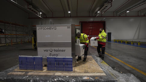 Cargo workers demonstrate the cold chain process for the handling of medicines and vaccines as they place boxes into a…