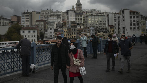 People, most wearing protective face masks to help protect against the spread of coronavirus, walk along Galata Bridge over the…