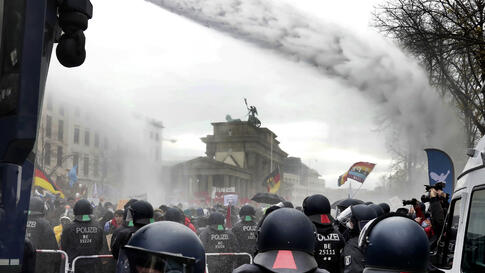 Police uses water canons to clear a blocked a road between the Brandenburg Gate and the Reichstag building, home of the German…