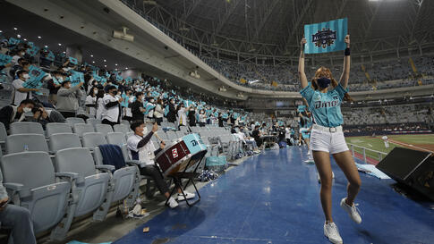 Cheerleaders and fans wearing face masks cheer during Game 2 of the Korean Series, the Korea Baseball Organization's…