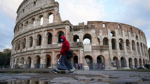 A friar walks past the Colosseum, in Rome, Friday, Nov. 20, 2020. (AP Photo/Andrew Medichini)