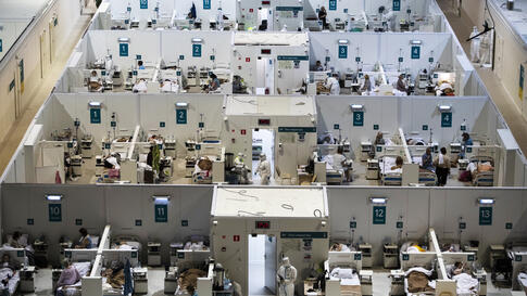 Medical workers and patients are seen in the treatment hall of a temporary hospital for coronavirus patients in the Krylatskoye…