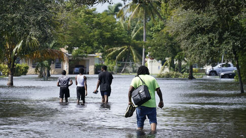 Residents walk a flooded street to reach their homes, Monday, Nov. 9, 2020 in Fort Lauderdale, Fla. Tropical Storm Eta caused…