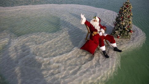 Issa Kassissieh, dressed as Santa Claus, waves next to a Christmas tree erected on a salt formation during filming for a…