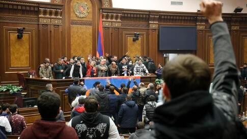 People shout as they broke into the parliamentary building protesting against an agreement to halt fighting over the Nagorno…
