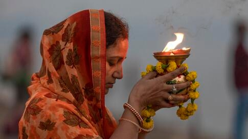 A Hindu woman offers prayers by the banks of the River Ganges, on the eve of Chhath Puja festival in Prayagraj, India, Thursday…