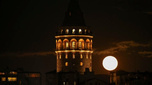 The moon rises over Istanbul's skyline dominated by the iconic Galata Tower, Wednesday, Dec. 30, 2020. (AP Photo/Emrah Gurel)