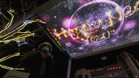 A visitor wearing a mask to protect from the coronavirus passes by Happy New Year greetings shown on a giant screen in Beijing…