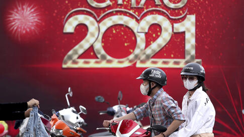 People wearing face mask o protect against the coronavirus ride a scooter in front of a banner welcoming New Year 2021 in Vung…
