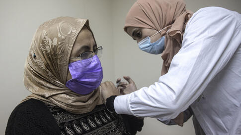 A Bedouin woman receives a Pfizer COVID-19 vaccine at a medical center in the Bedouin local council of Segev Shalom near the…