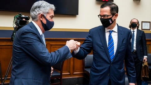 Federal Reserve Chairman Jerome Powell fist bumps Treasury Secretary Steven Mnuchin after a House Financial Services Committee…