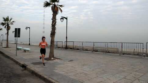 A woman runs on the empty waterfront promenade as the country begins a three-week lockdown to limit the spread of coronavirus…