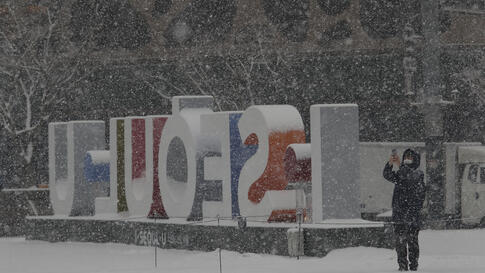 A man wearing a face mask as a precaution against the coronavirus takes photos in the snow at City Hall Plaza in Seoul, South…