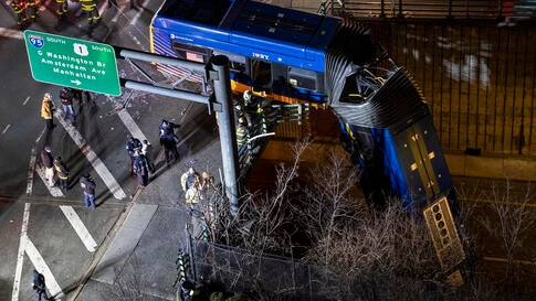 A bus in New York City which careened off a road in the Bronx neighborhood of New York is left dangling from an overpass Friday…