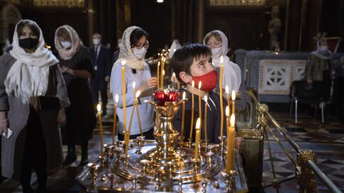 A boy and other parishioners wearing face masks to protect against coronavirus, attend the Christmas Mass in the Christ the…