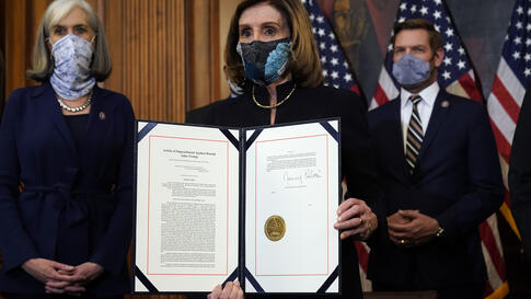 House Speaker Nancy Pelosi of Calif., displays the signed article of impeachment against President Donald Trump in an…